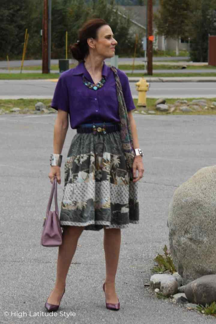 Nicole in tired skirt, purple shirt, matching scarf and accessories