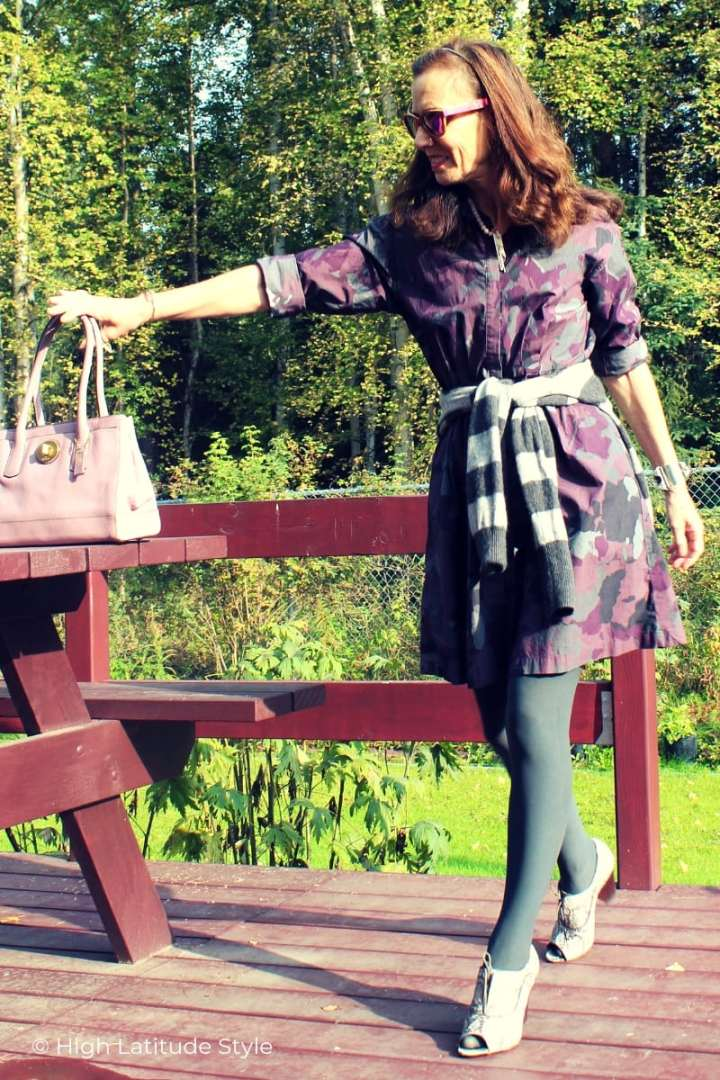 style book author in dress with opaque tights putting a bag on a table