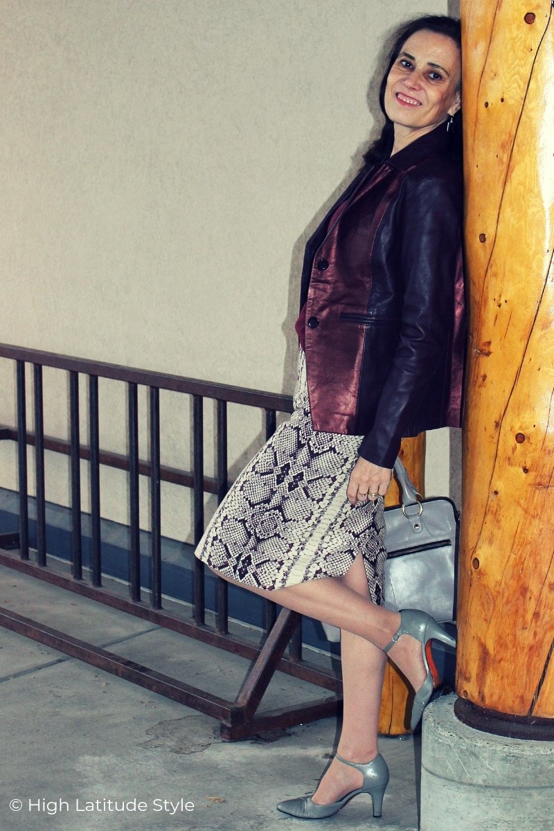 older woman in leather jacket with trendy skirt in burgundy, gray and brown