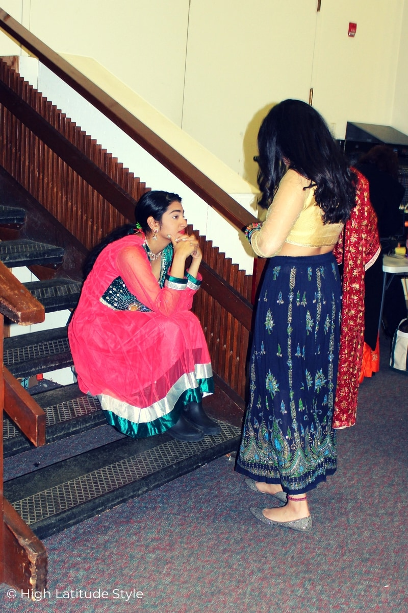 Indian dancers in costumes waiting on a staircase