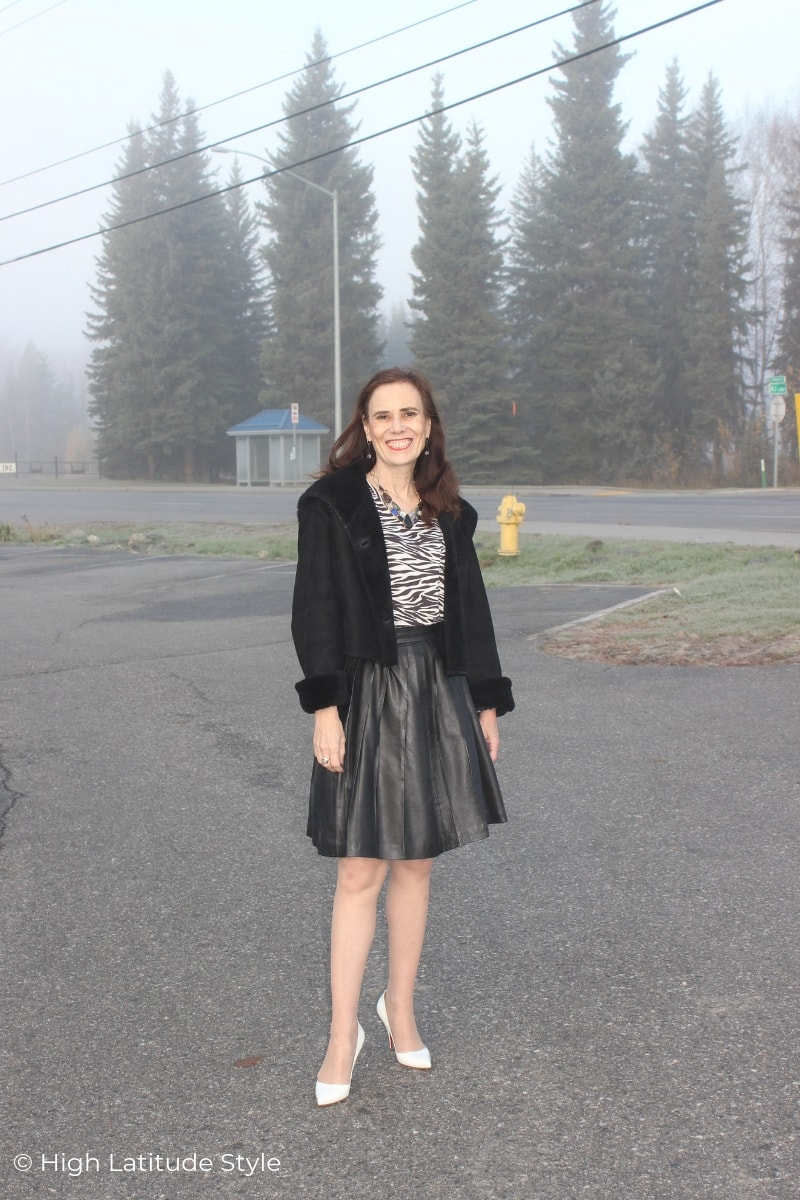 Alaskan fashion blogger in pleated leather skirt, zebra top and shearling hoodie in the fog