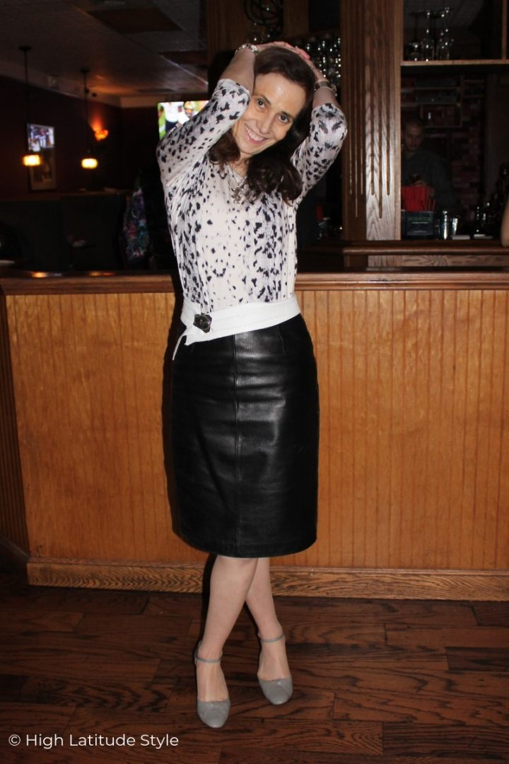 fashion blogger posing in a black, gray and white outfit with leather skirt and animal print top