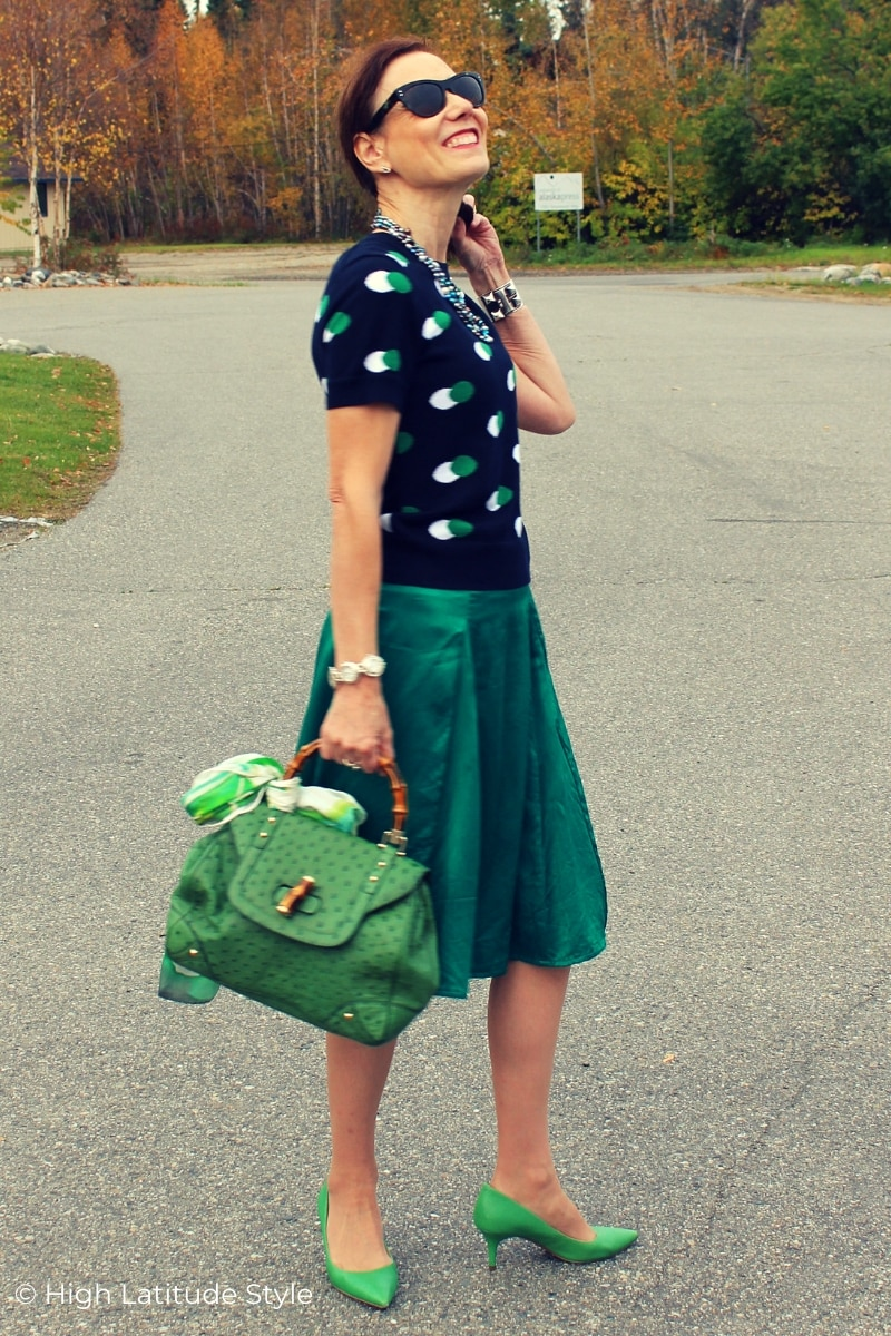 mature woman in A-line skirt, polka dot sweater, green heels