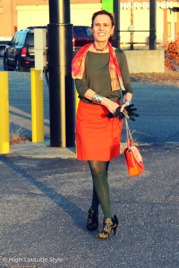 midlife woman in orange skirt, olive top, tights shoes, gloves and scarf in both colors