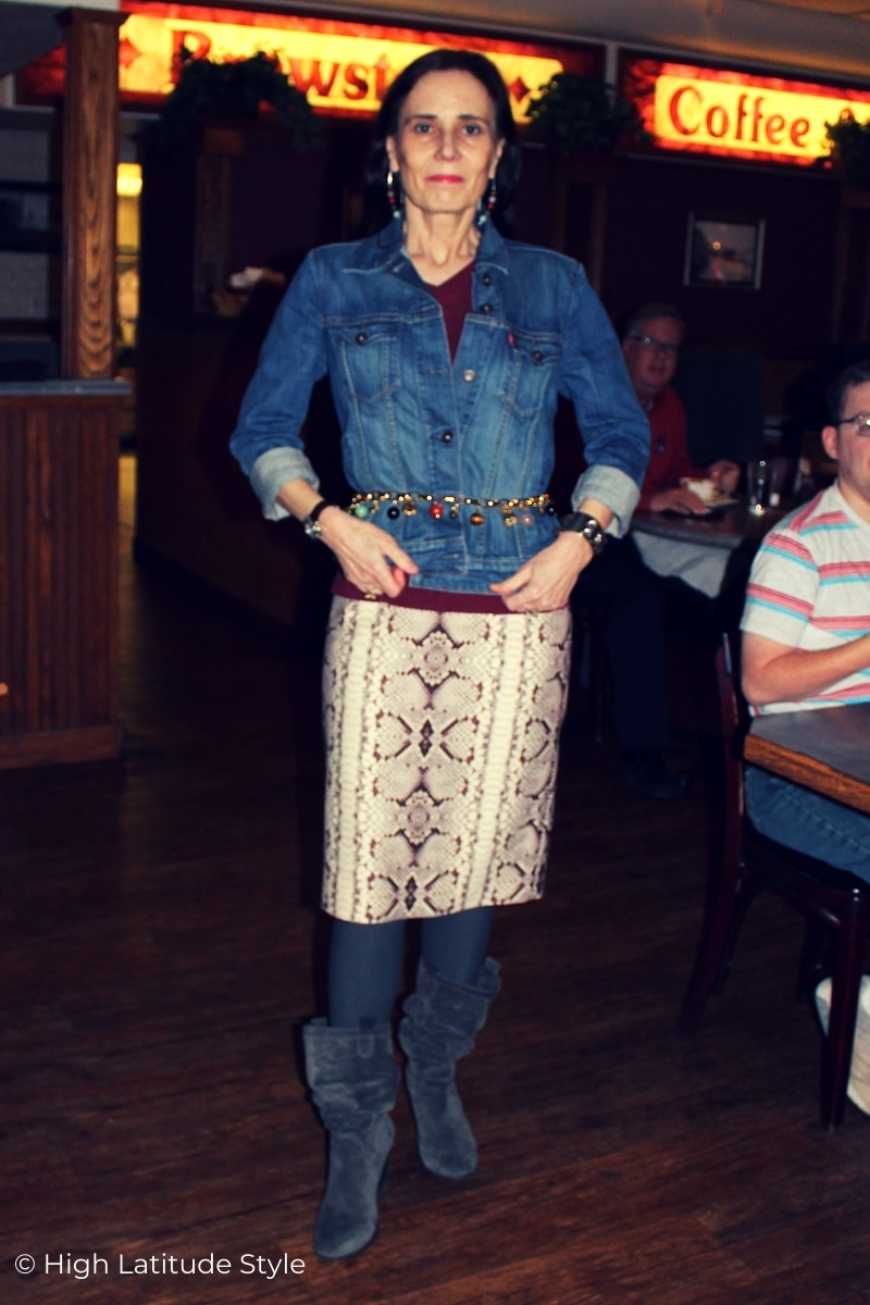 stylist in street chic with trendy snake print, denim, suede with gemstone hangers