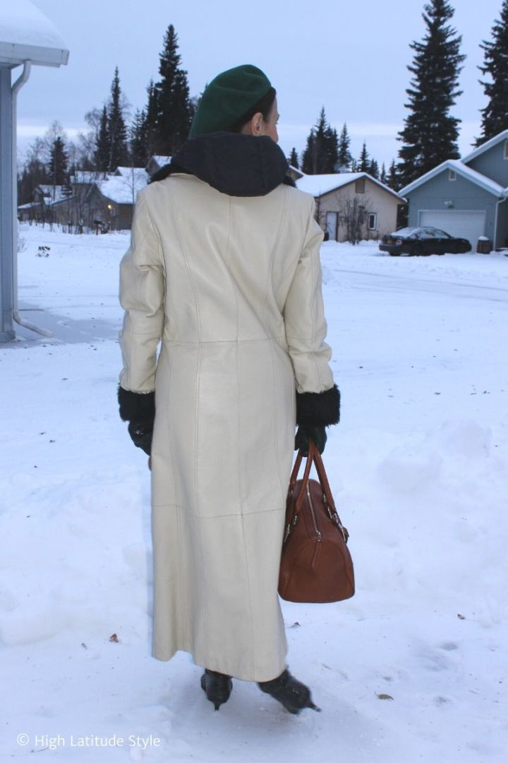 older woman in long leather coat with faux fur trim looking down the street