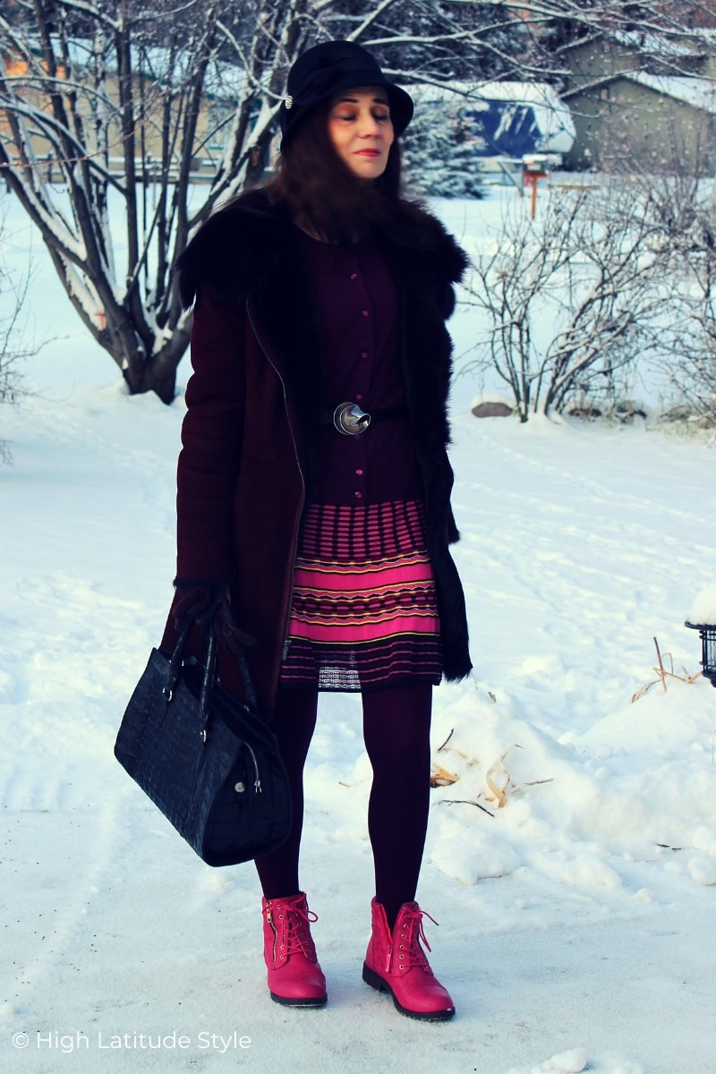 fashion blogger waiting in a winter scene in hat, coat, dress, cardigan, tights and zipper shoes