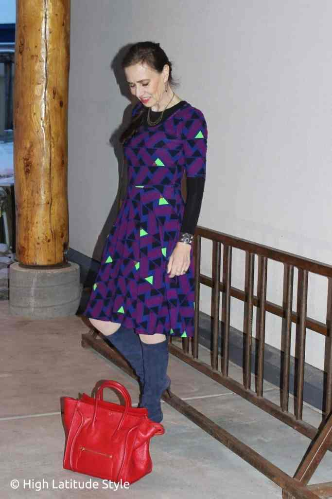 street style blogger in printed dress, blue sweater, and boots with red tote
