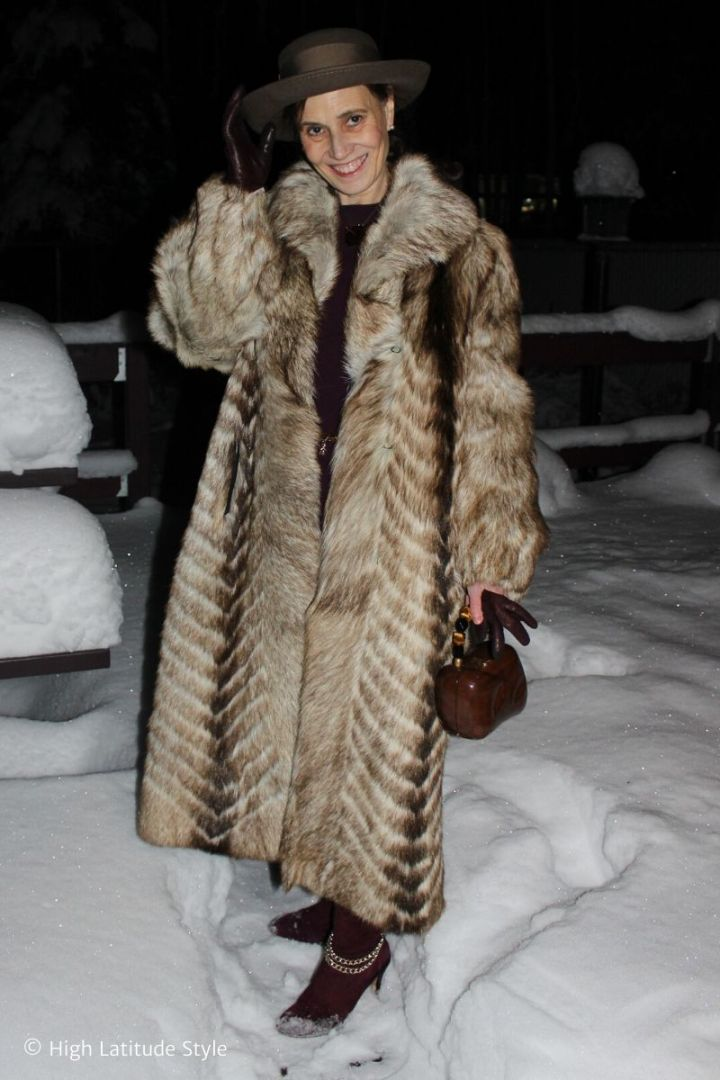 Style book author in long winter coat, boots, dress with gloves, wooden bag and hat