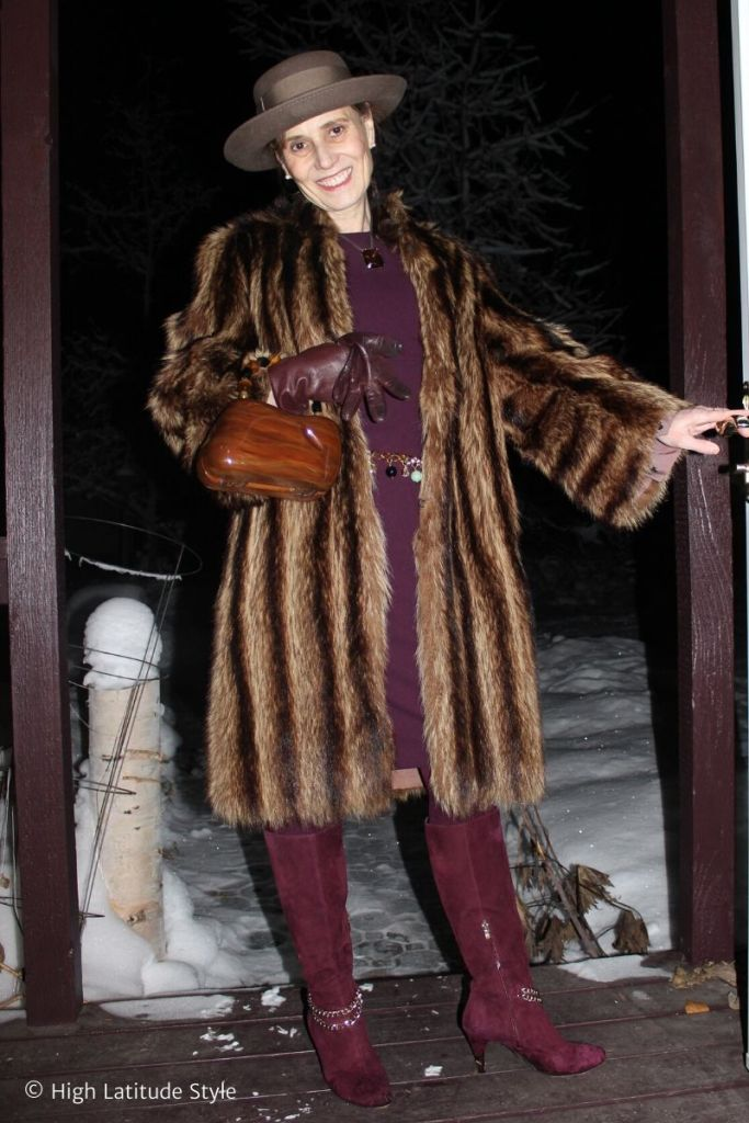 style blogger in winter coat, sheath dress, boots and hat with wooden bag and gloves