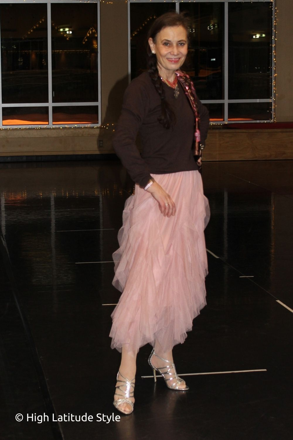 style book author in pink tulle skirt, braun sweater, matching scarf, silver sandals