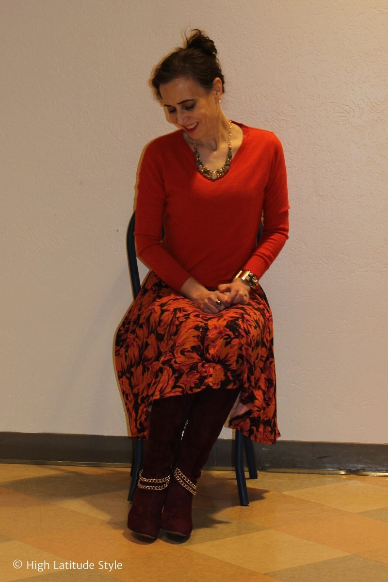stylist sitting on a chair in boot with burgundy orange skirt, v-neck sweater, necklace