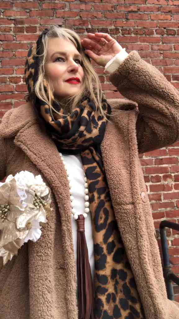 Cindy Scurry in a trendy teddy coat with leopard print scarf and winter white sweater