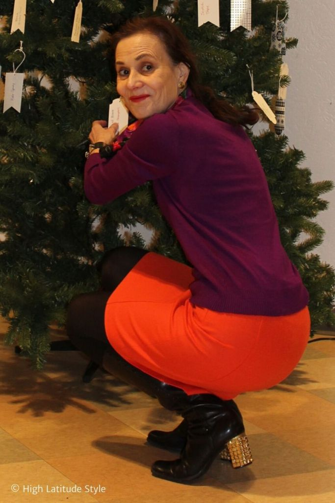 mature woman kneeling to decorate a Christmas tree