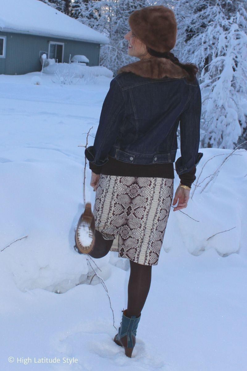 Alaskan woman standing on 1 leg showing the snow under the sole of her boots