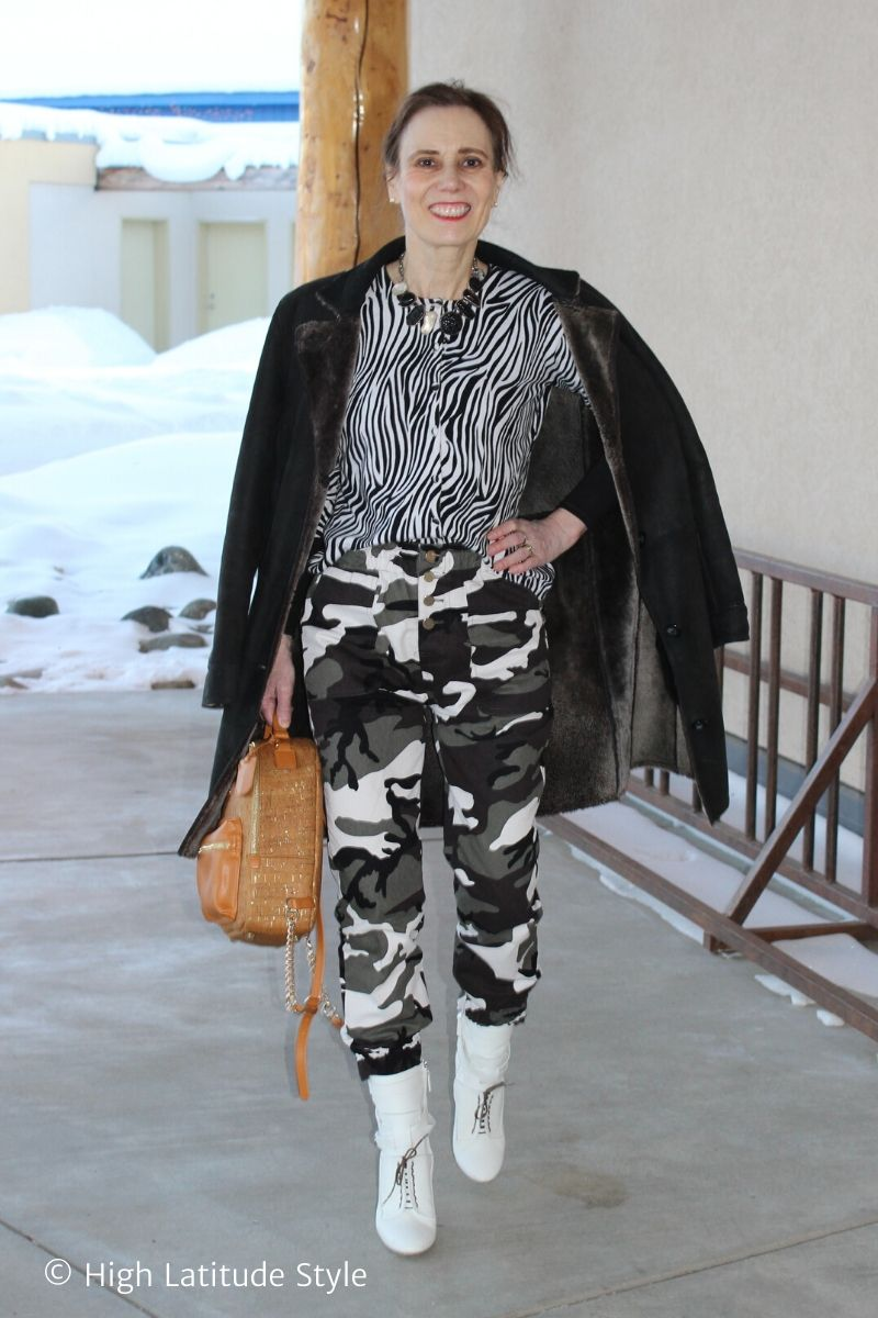 Alaskan woman in black and white pants, cardigan, necklcae with black top and coat