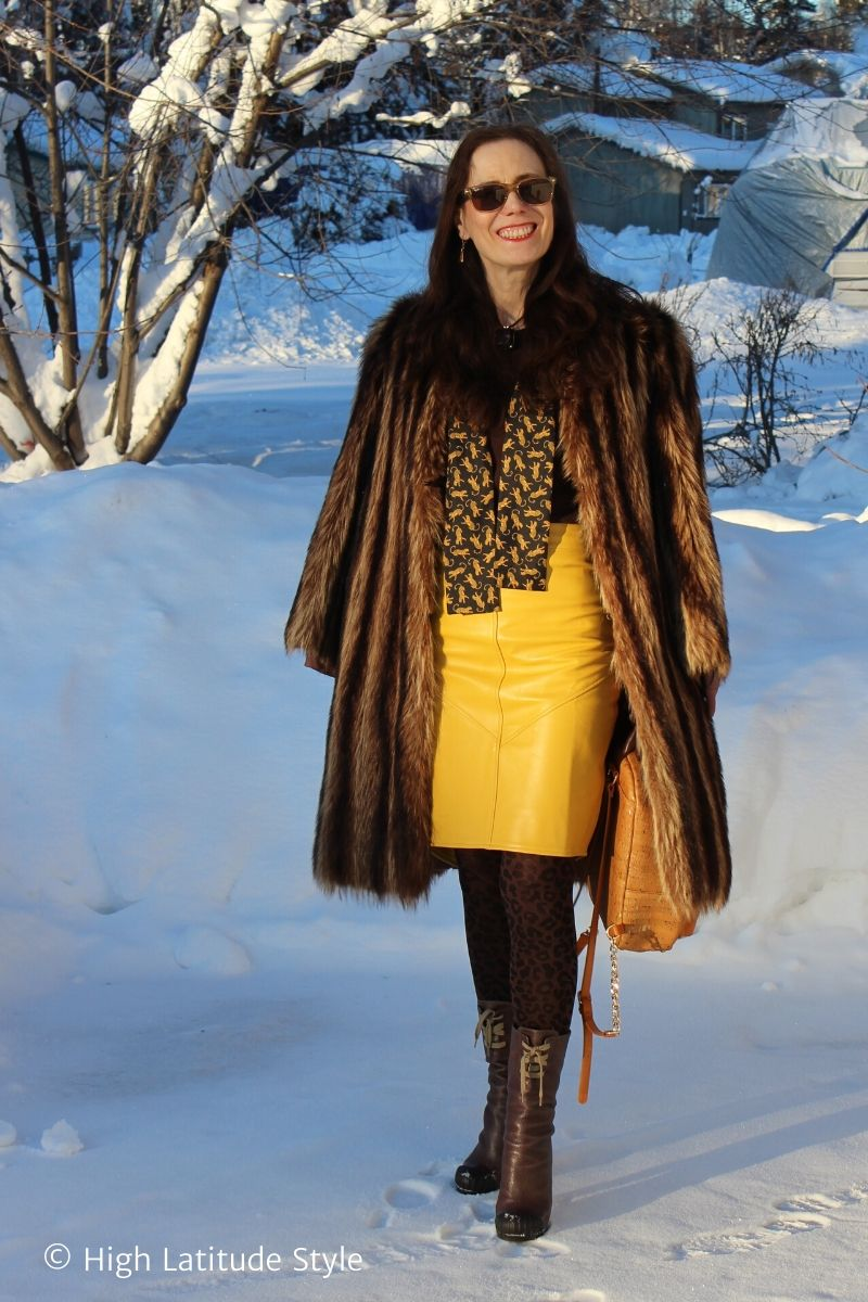 Alaskan blogger in thick coat, leather skirt, leopard tights, sweater, scarf and boots in the snow