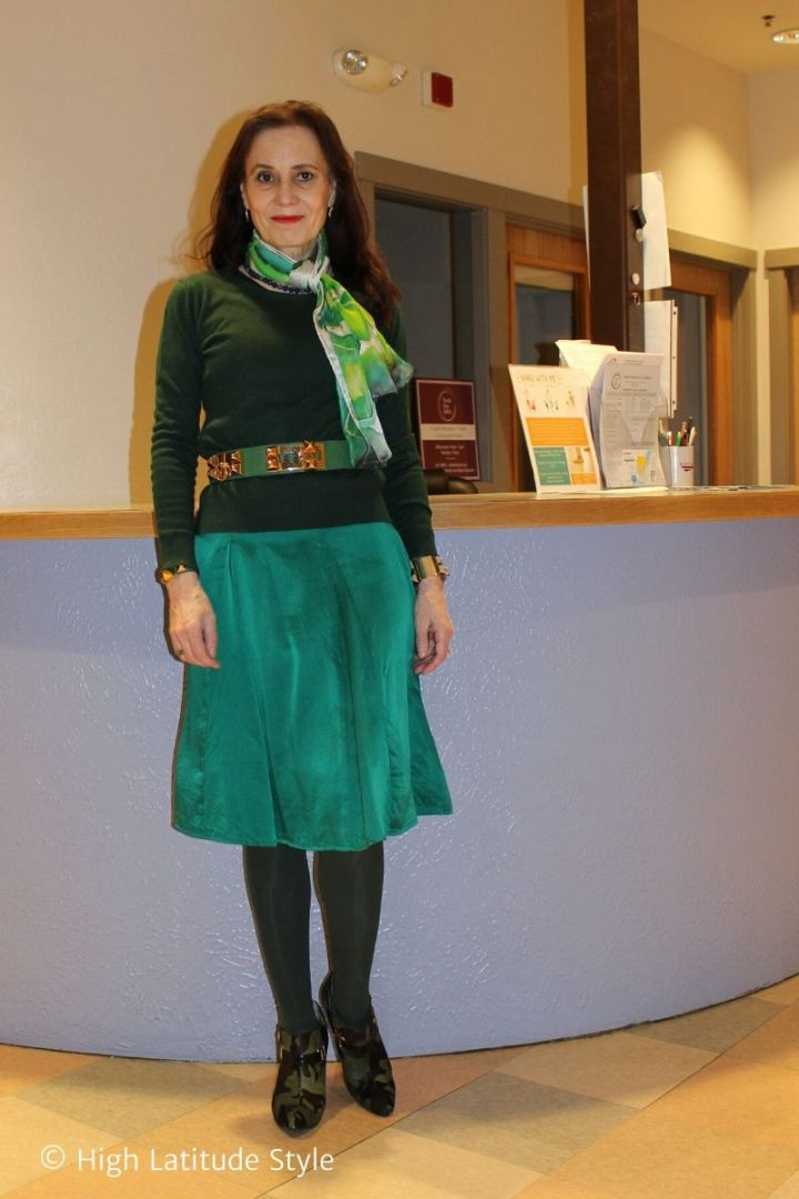over 50 years old woman in monochromatic green outfit of skirt, sweater, scarf, tights, belt and footwear