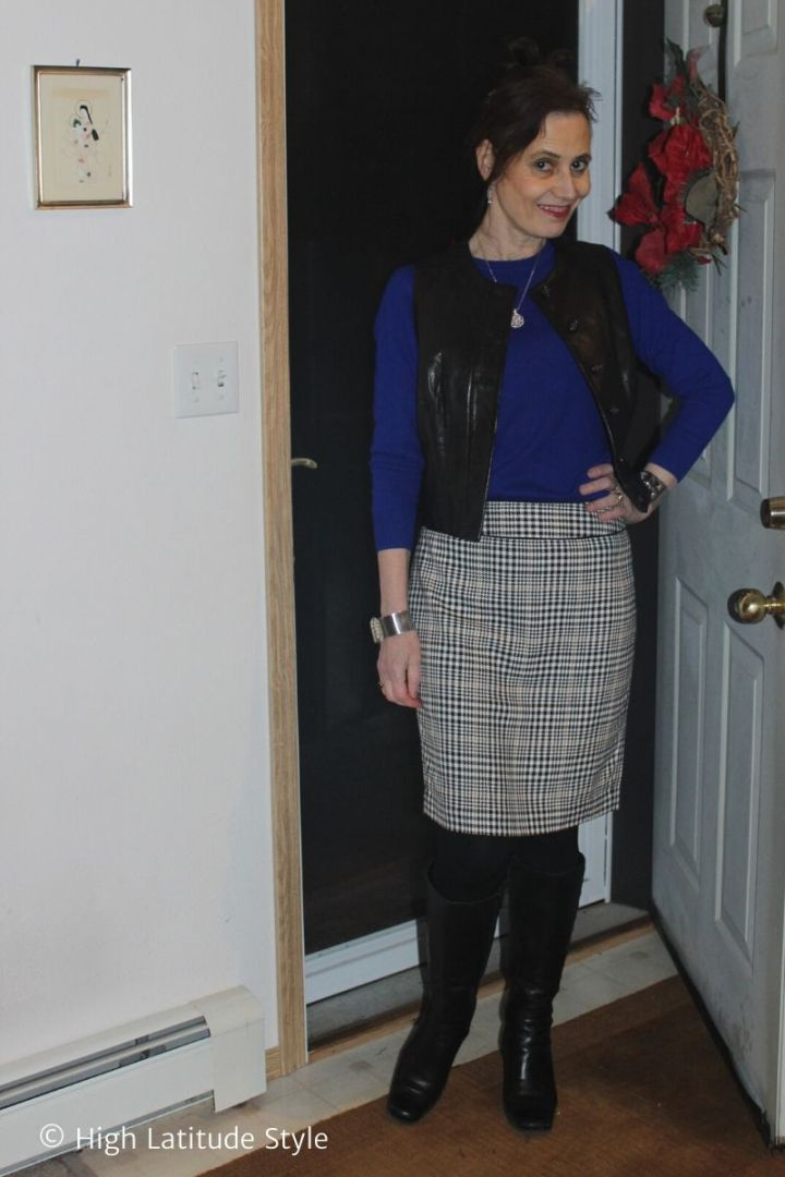 fashion blogger in winter look of blue top, plaid skirt, tall boots, black tights