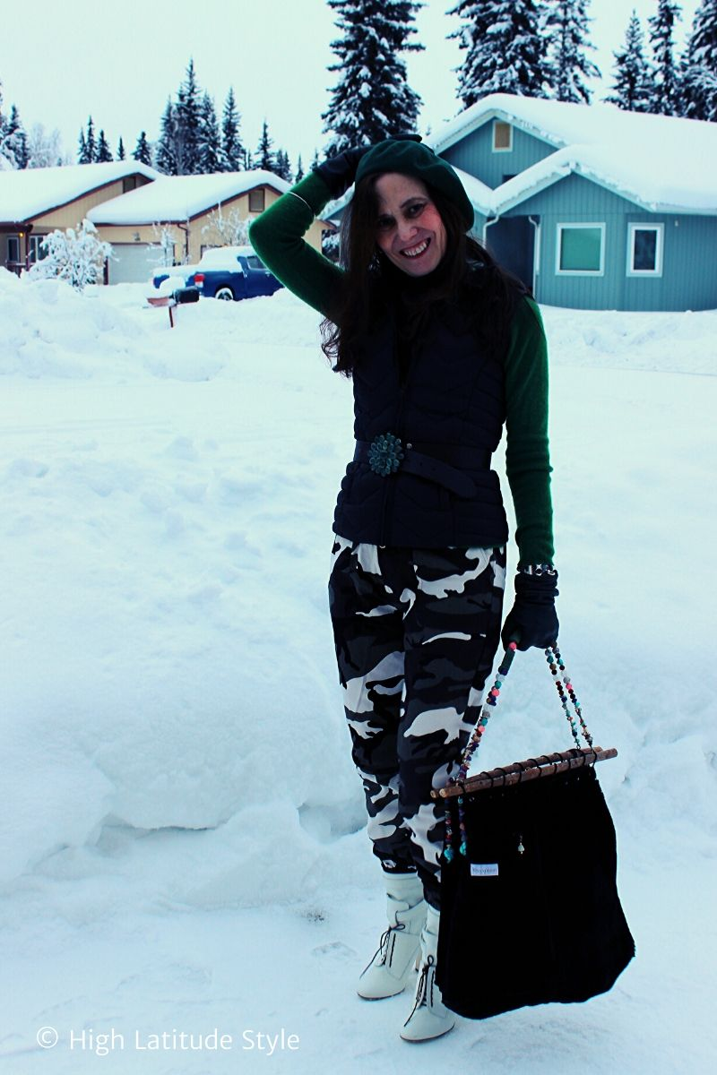 blogger Nicole in snow camo trouser posing in the snow with down vest, green sweater and beret, white boots