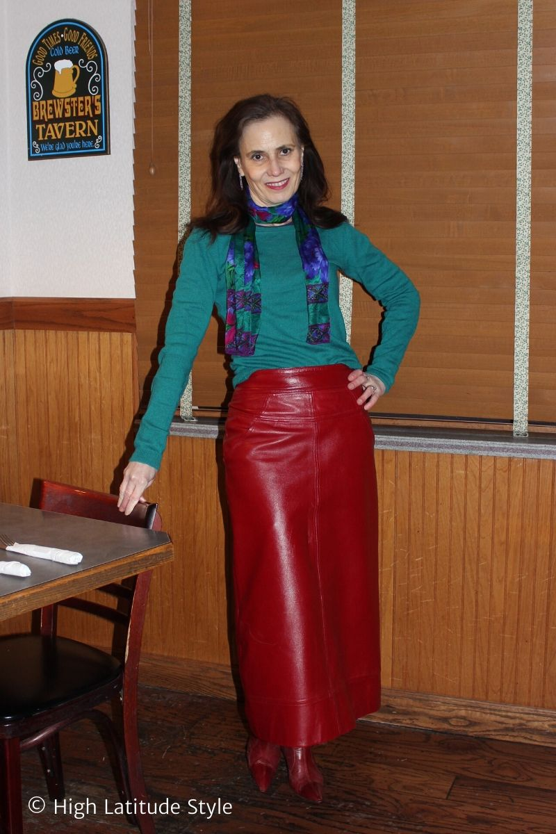 stylist in long leather skirt, sweater top, scarf and red ankle boots