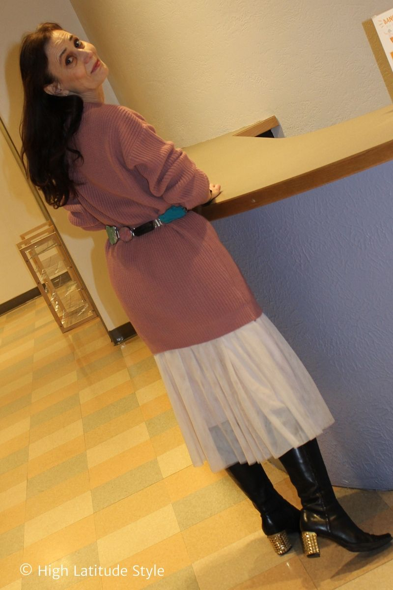 stylist in tulle skirt with knitted top, knee-high boots, belt
