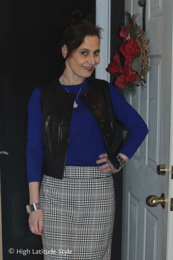 Fairbanks stylist in winter meeting outfit with hounds tooth skirt, royal blue sweater, short leather vest, jewelry