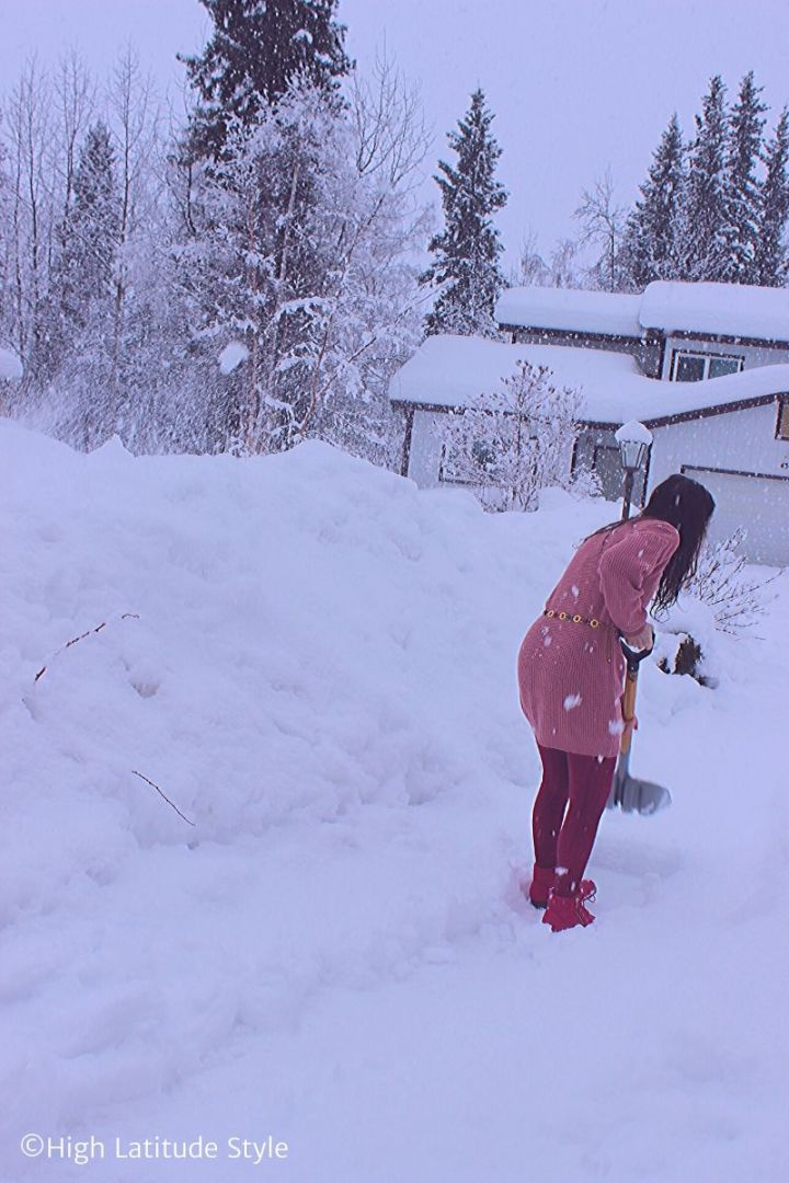 Alaskan snow covered street, spruce and house with woman in foreground