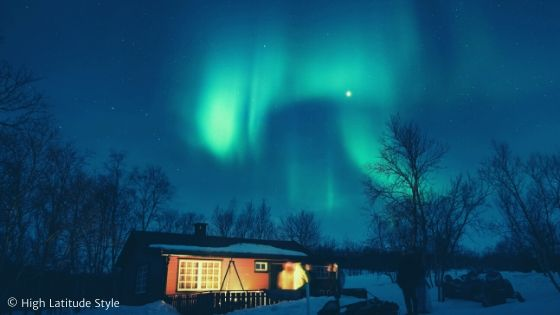 Aurora borealis in Moon light over a lonely cabin