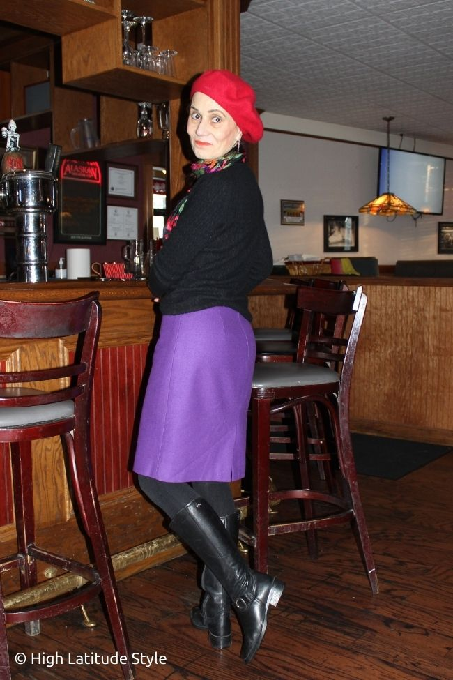 stylist in purple skirt, red beret, black tights, boots, sweater and colorful scarf