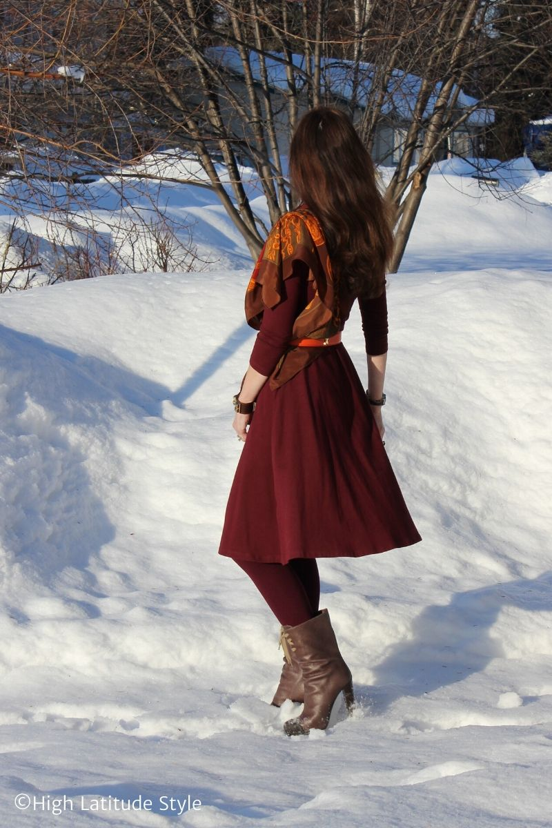 Alaskan woman walking in the snow in a fit-and-flare dress with scarf