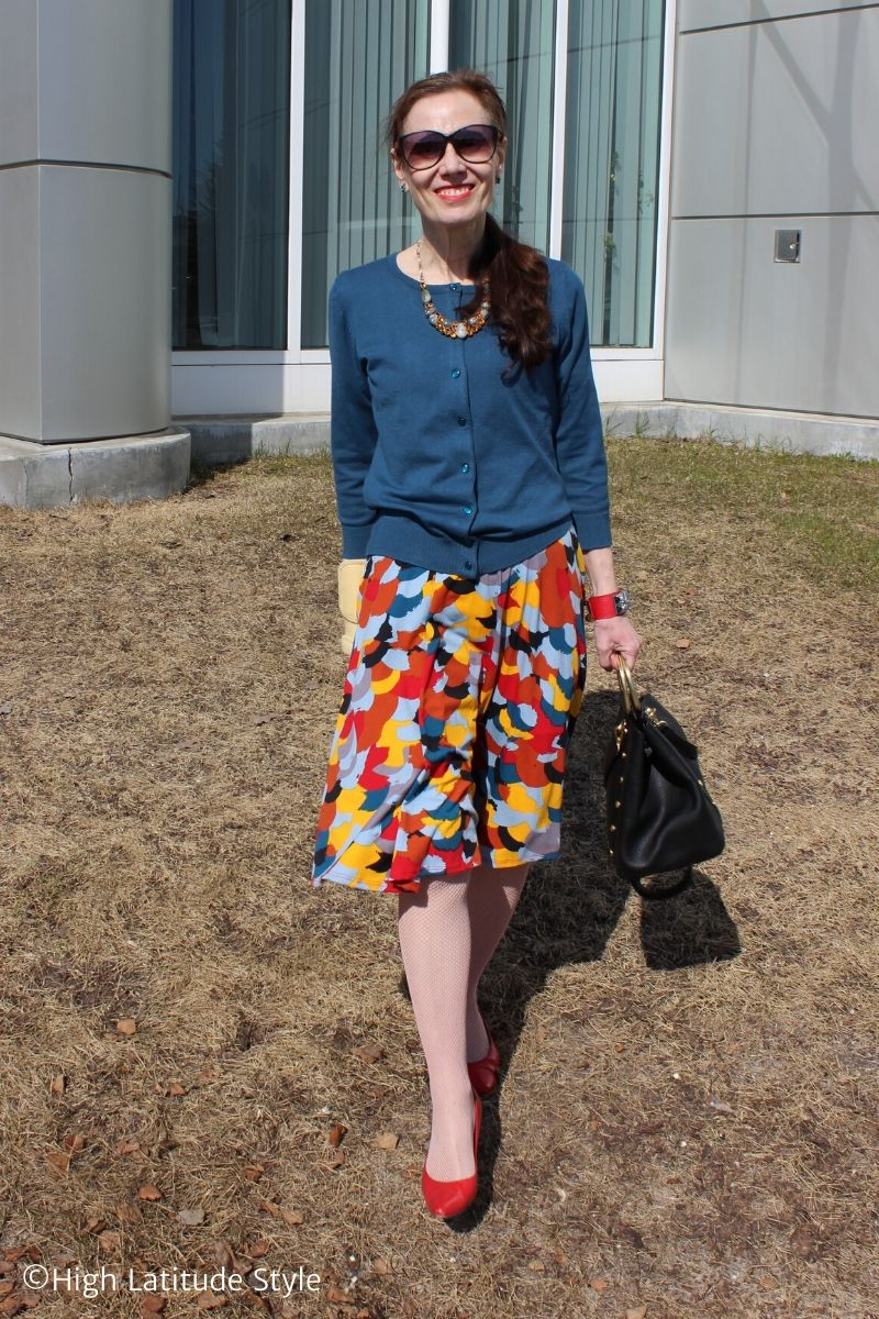 fashion blogger wearing a multi-color dress as skirt with cardigan
