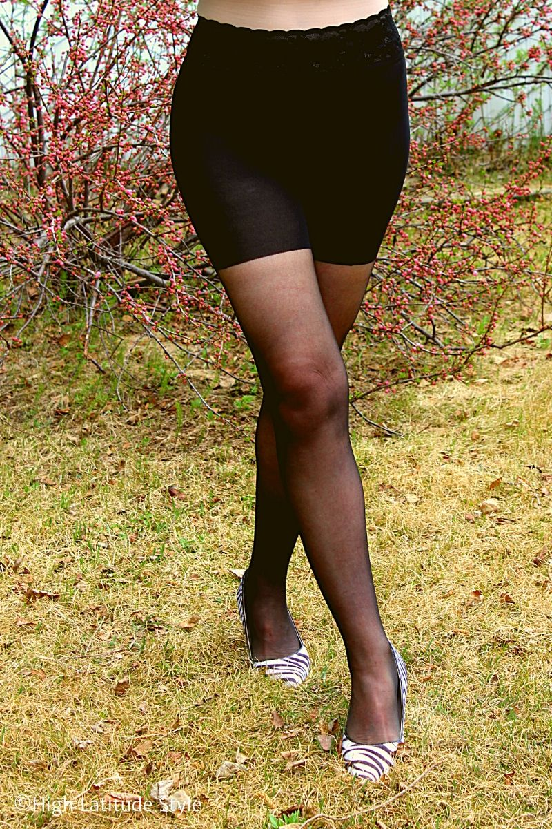 legs and hips of a woman wearing sheer  black pantyhose with woven-in biker top