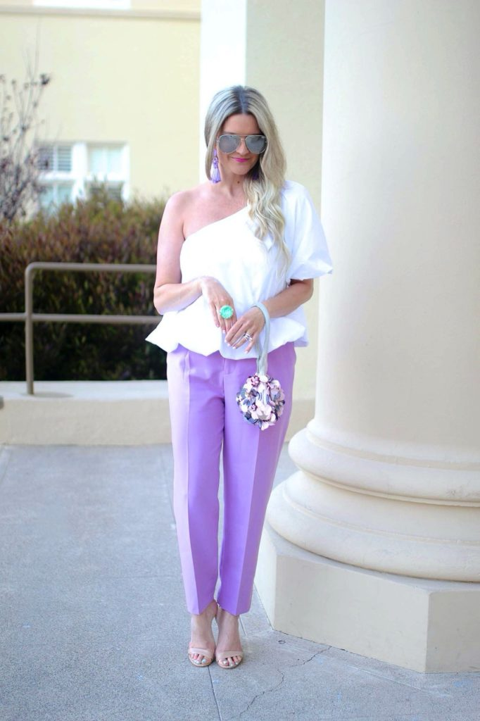 Shauna in peplum top and lavender dress pants with sandals and flower embellished bag