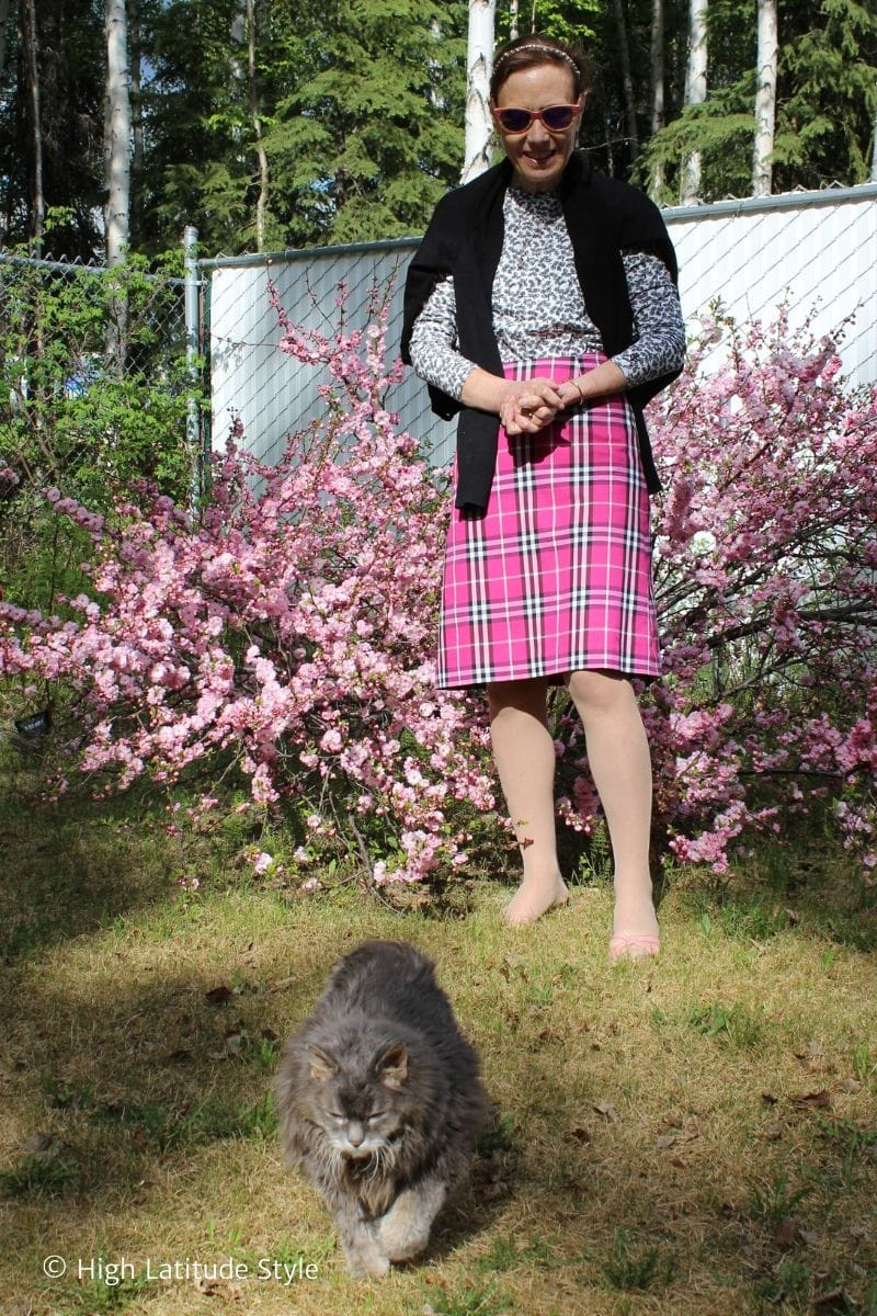 blogger in pink a-line skirt, leave print top, jacket over shoulders, headband