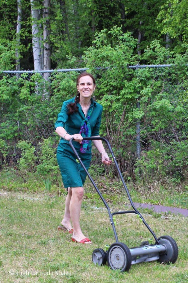 Alaskan blogger in shirt dress pushing a lawn mower