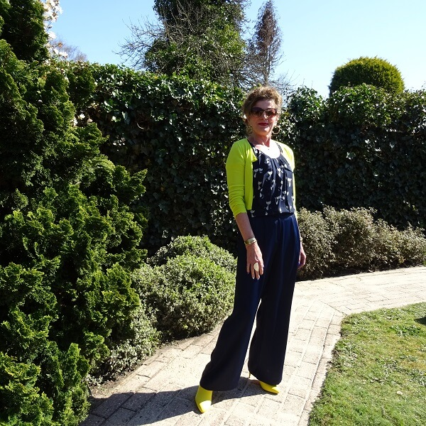 blogger Nancy in navy pants and top, neon yellow booties and cropped cardigan