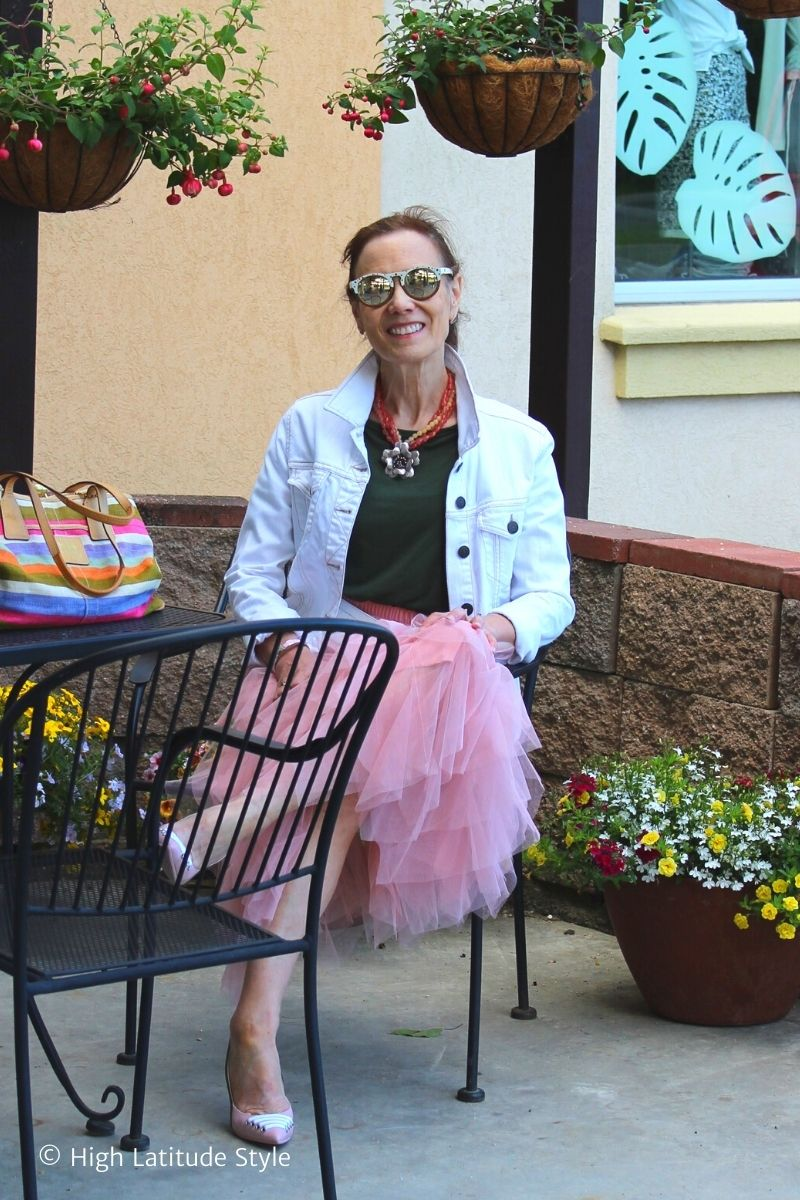 blogger Nicole sitting on a deck in tulle skirt, top, jacket, sunnies