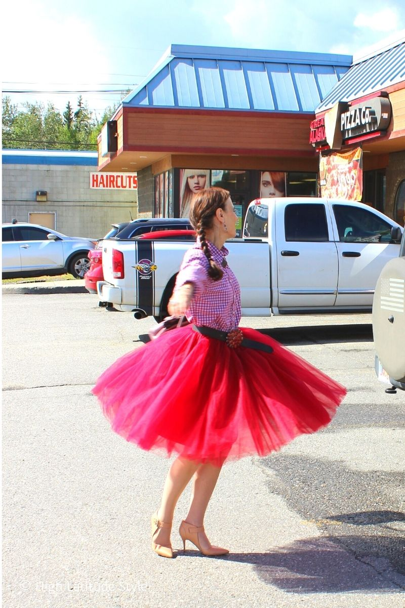 ballroom dancer Nicole twilling in a tutu with gingham shirt in a parking lot