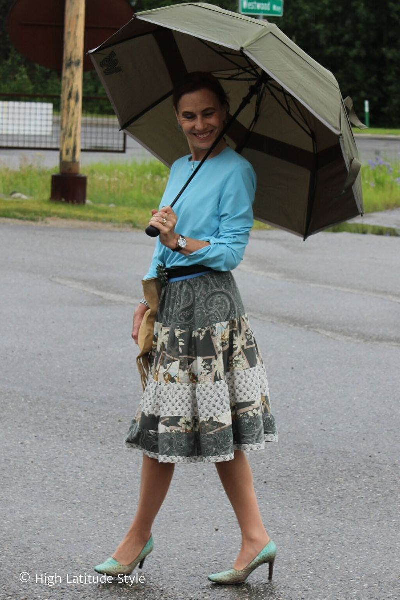 over 50 years old woman in blue blouse, olive skirt and umbrella