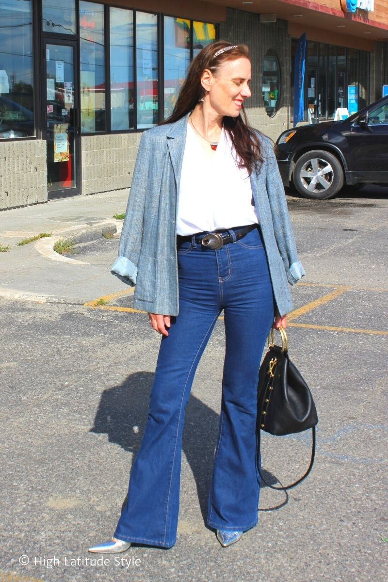 over 50 years old woman in flared jeans, white blouse, belt, jacket, high heels