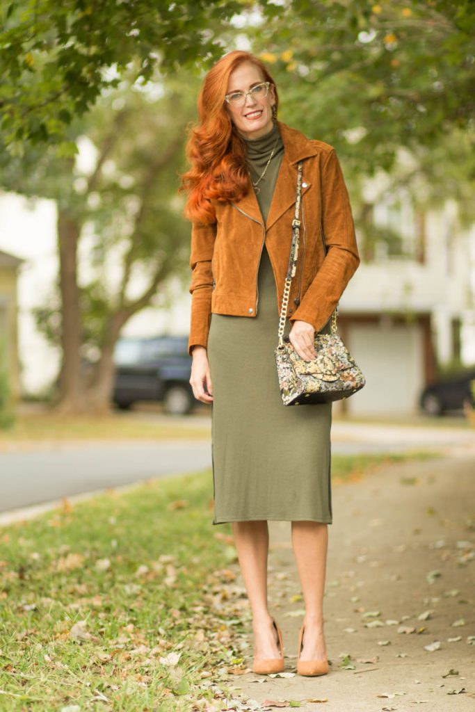 Jess in olive turtleneck dress, tan pumps, snake print shoulder bag and tan suede motorcycle jacket