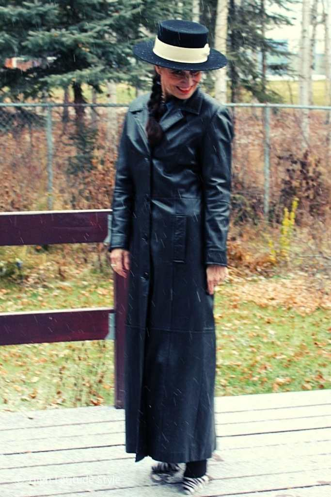 over 50 years old fashion blogger in maxi leather coat and boater hat