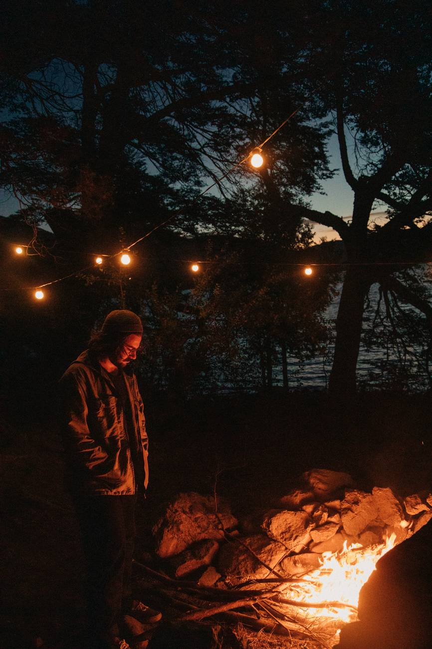guy in winter gear in front of a bonfire at night in winter