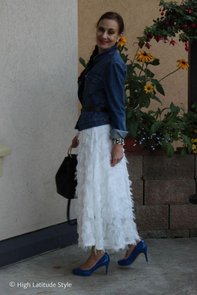 stylist in fall trendy look of midi skirt, pantyhose, denim and bucket bag