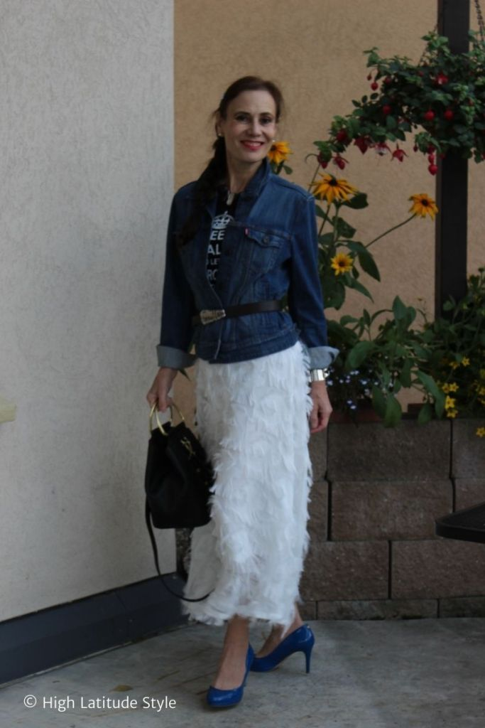 style blogger in white bottom layered top of graphic T-shirt, denim topper, belt, bucket, black pumps
