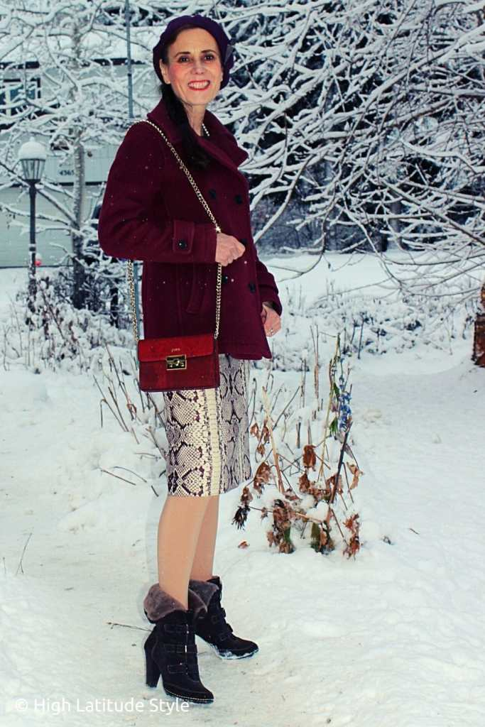 over 50 years old fashion blogger in winter peacoat, skirt, tights, boots with designer vegan handbag