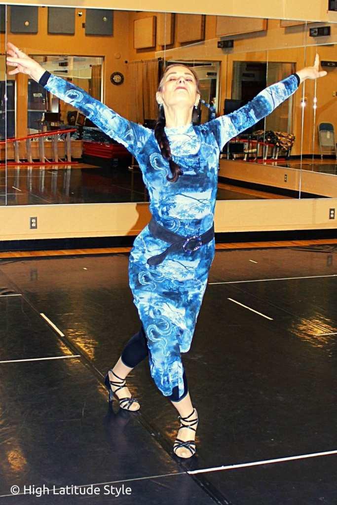 dancer striking a pose in a blue bodycon mesh dress over leggings