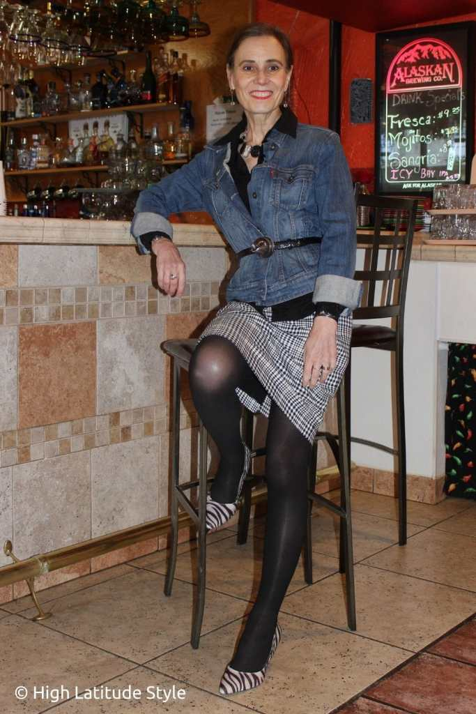 stylist in all neutral look of houndstouth skirt, jean jacket, semi opaque tights, silk shirt, zebra pumps