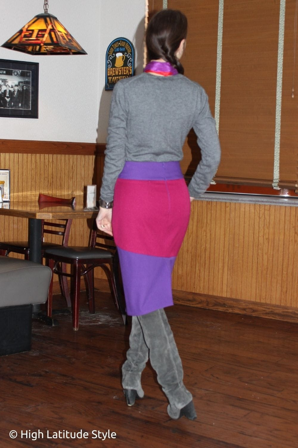 style influencer in gray boots and sweater with purple with fuchsia assymetric pencil skirt